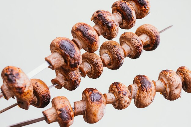 Marinated pieces of  mushrooms are grilled on charcoal skewers