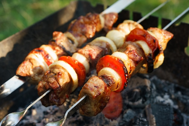 炭火でバーベキューグリルで調理した金属串にトマトと玉ねぎを添えた肉のマリネ