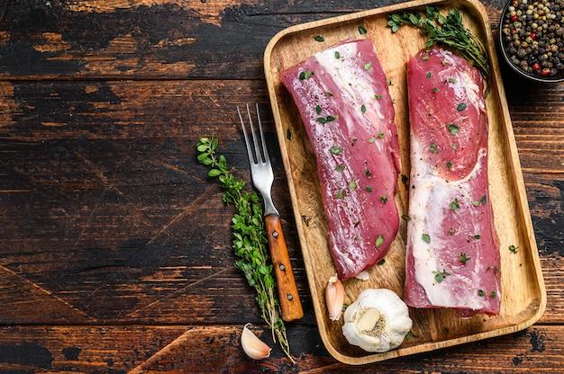 Мясной стейк из свиной вырезки, маринованный с тимьяном. темный деревянный фон. вид сверху. скопируйте пространство.