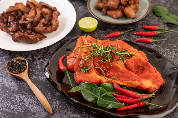 Marinated pork used in cooking, complete with chili peppers kaffir lime leaves in a black plate