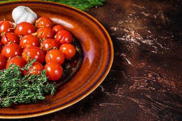 마늘과 백리향을 곁들인 소박한 접시에 절인 보존 체리 토마토. 어두운 배경입니다. 평면도. 공간을 복사합니다.