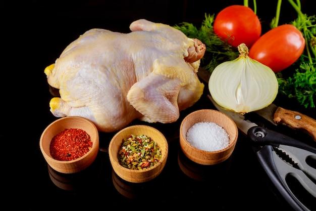 Marinated raw chicken on a dark background. raw chicken and vegetables