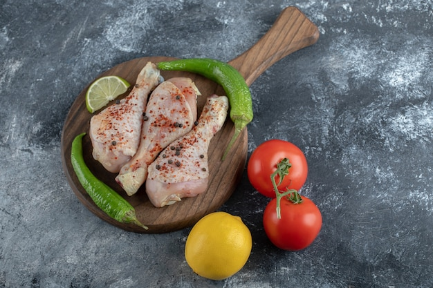 Marinated raw chicken drumsticks with vegetable on grey background.