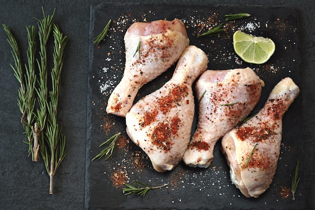 Marinated raw chicken legs on a dark stone board.