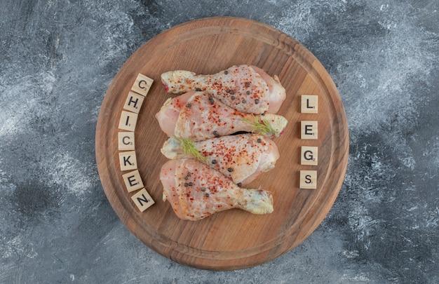 Cosce di pollo crude marinate su tavola di legno.