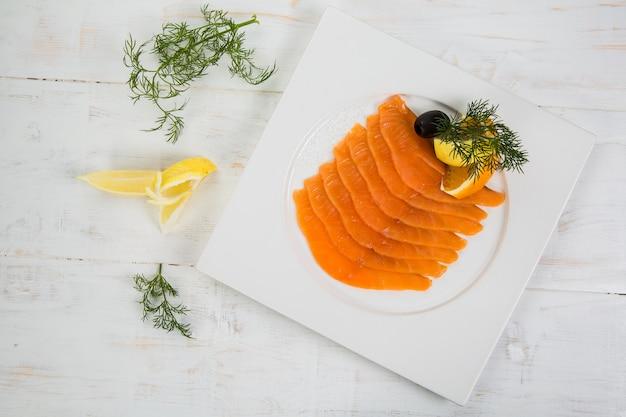 レモンとオレンジのマリネサーモン。ハーブで飾ります。白い木製backfround