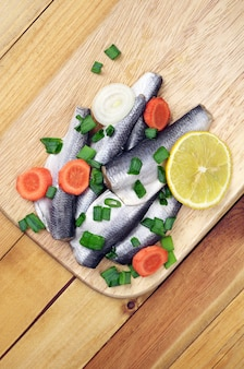 Marinated salted fish on a cutting board on table