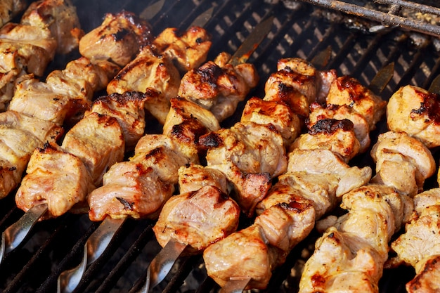 Marinated shashlik preparing on a barbecue grill over charcoal. shashlik or shish kebab