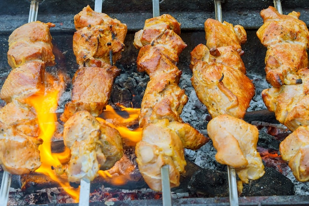 Marinated shashlik preparing on a barbecue grill over charcoal.