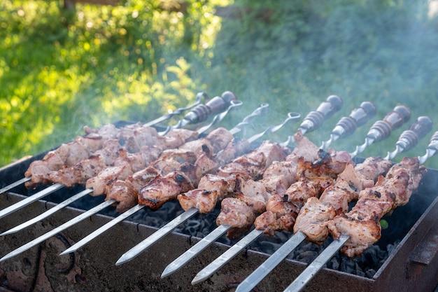 Marinated shashlik or shish kebab preparing on a barbecue grill over charcoal.