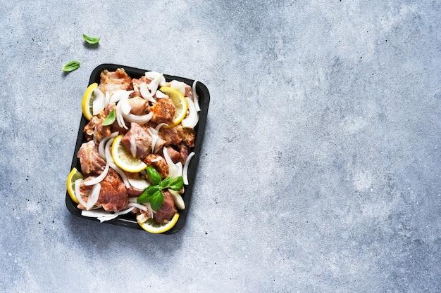 シシカバブのタマネギとレモンのマリネ。トレイにスパイスが入った豚肉。