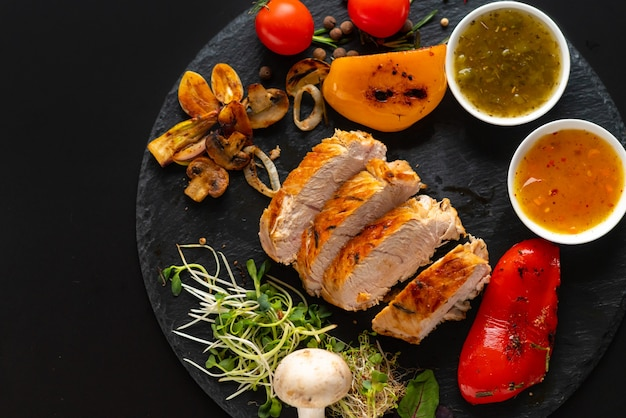 Marinated sliced grilled chicken breast with roast vegetables, side dishes of savory sauce and salad sprouts viewed from above on black