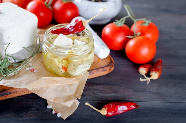 Marinated spicy  feta in a jar and vegetables for salad.