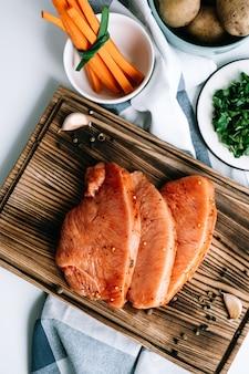 당근 스틱과 허브 테이블에 나무 보드에 향신료와 절인 된 칠면조 스테이크.