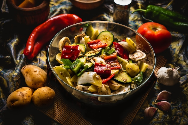 Marinated vegetables in a glass bowl and other ingredients to make vegetable skewers.