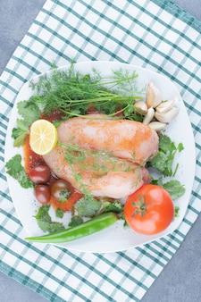 Маринованная целая курица на тарелке с овощами.