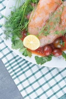 야채와 함께 접시에 절인 된 전체 닭고기입니다.