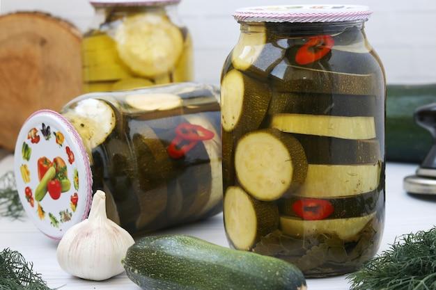 テーブルの上にあるガラスの瓶にマリネしたズッキーニ、クローズアップ、水平方向、冬の野菜の収穫