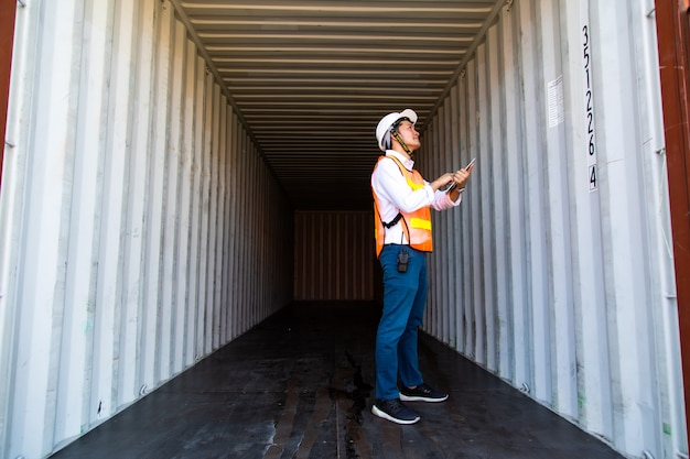 Концепция морского и транспортного страхования. инженер проверяет контейнер в ящике в порту отгрузки. бизнес-логистика концепция импорта и экспорта.
