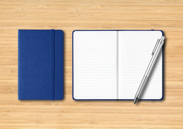 Marine blue closed and open lined notebooks with a pen. mockup isolated on wooden background