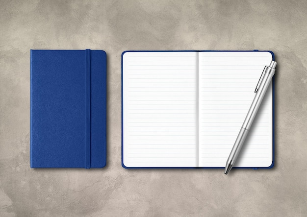 Marine blue closed and open lined notebooks with a pen