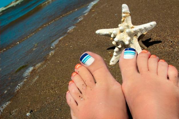 Морской синий полосатый разноцветный педикюр с морской звездой на песке пляжа