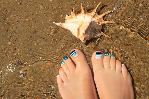 ビーチの砂の上にヒトデとマリンブルーの縞模様の色とりどりのペディキュア