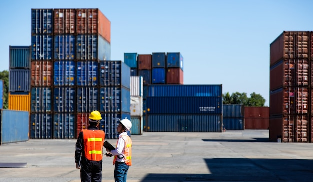 Marine and carrier insurance concept. foreman control loading containers box at shipping port. business logistic import and export concept.
