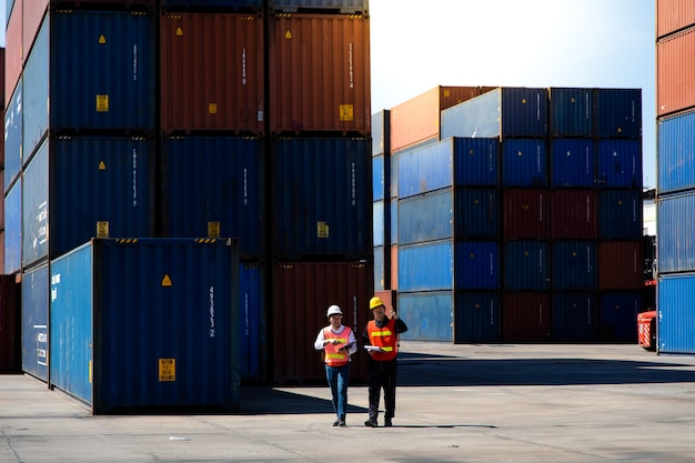 Marine and carrier insurance concept. two harbor man working at container yard. foreman control loading containers box at shipping port. business logistic import and export concept.