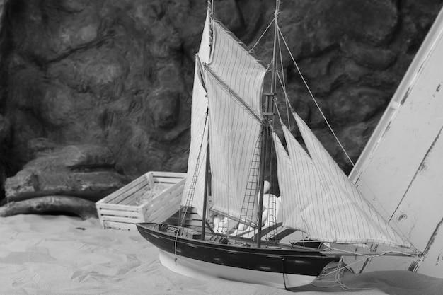 Морская концепция - милая миниатюра лодки на песке в монохромном стиле