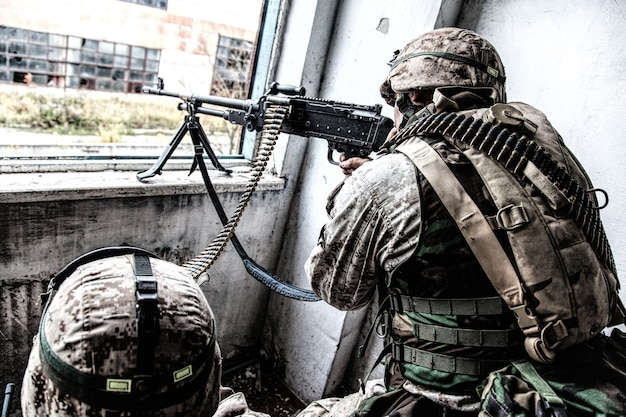Marine corps machine gun crew shooting through window in ruined building during city firefight. army machine gunner attacking enemy with aimed, direct fire while his comrade holding ammunition belt