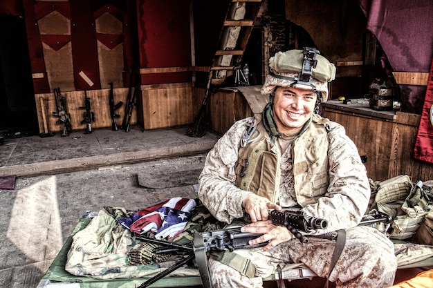 Marine corps machine gunner smiling, disassembling, making maintenance of service weapon, checking gun barrel after cleaning at improvised outpost in abandoned building