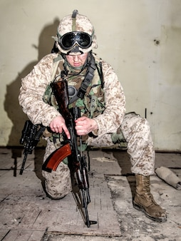 Marine disassembling, repairing, making maintenance of automatic assault carbine in combat conditions. counter terrorist squad fighter checking and neutralizing illegal weapons founded during raid
