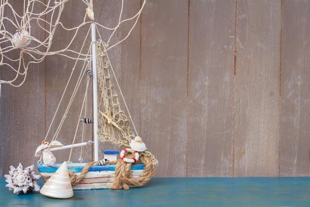 Морская жизнь с ракушками и лодкой, копией пространства на сером деревянном фоне