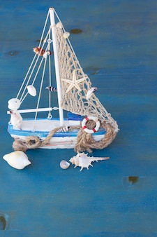 Marine life with seashells and fishing boat on blue wooden background
