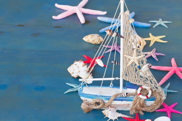 Marine life with seashells,  starfish and boat , copy space on blue background