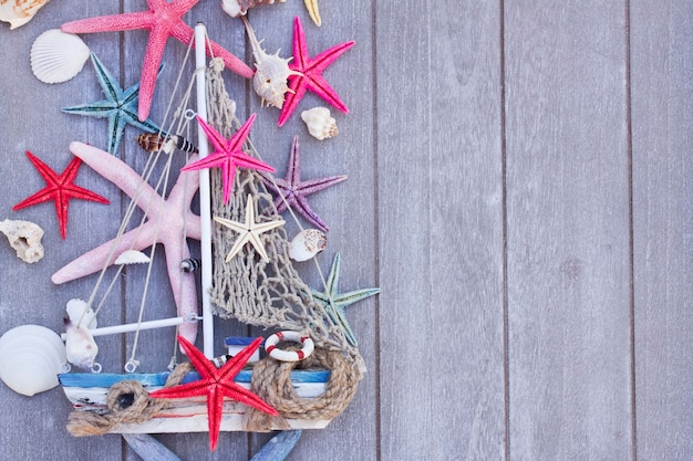 Marine life with seashells,  starfish and boat , copy space on wooden planks