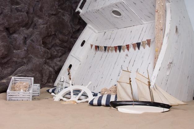 Морской или морской тематический натюрморт, изображающий затонувший корабль с деревянной лодкой, перевернутой в песок, с корабельным колесом, фонарем, опрокинутой игрушечной яхтой и разбросанными вокруг деревянных ящиками.