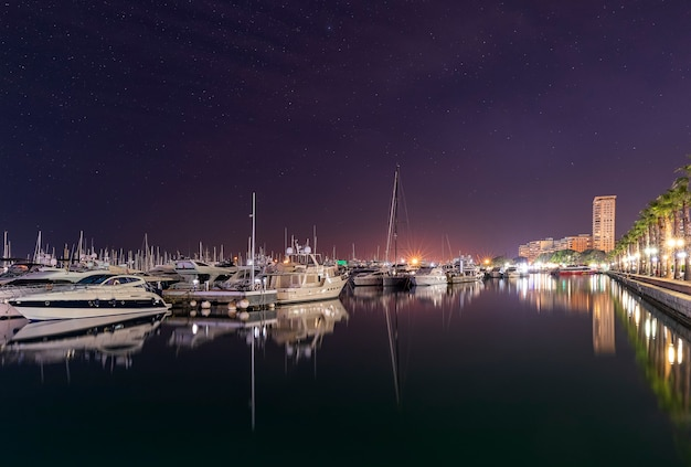 Marine port in alicante at night with luxury yachts, ships and fishing boats are standing in rows in harbor