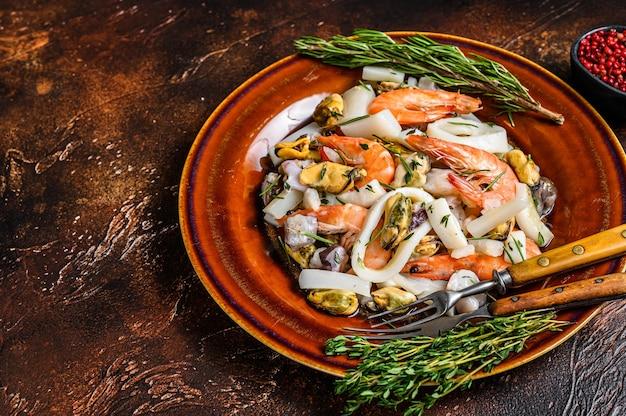 도마에 새우, 새우, 홍합, 오징어, 문어를 곁들인 해양 해산물 칵테일. 어두운 나무 테이블. 평면도.