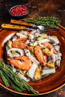 Коктейль из морских морепродуктов с креветками, креветками, мидиями, кальмарами и осьминогами на разделочной доске.