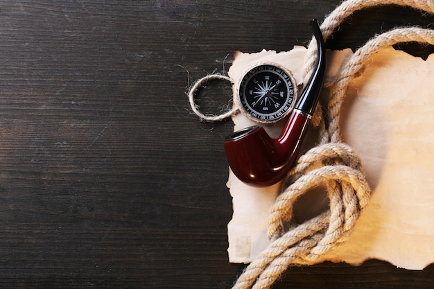 Marine still life pipe, compass, rope and sheet of paper on wooden background