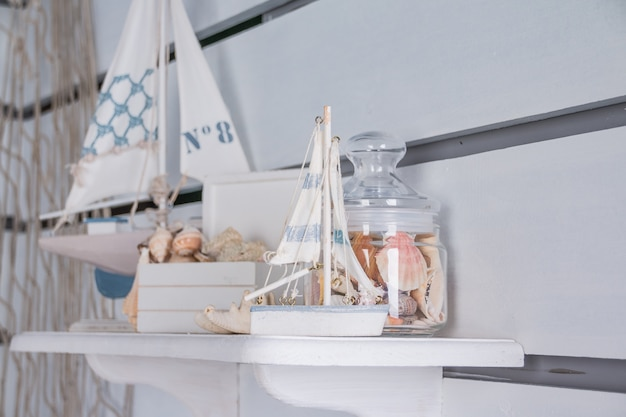 Marine still life with ships and piece of coral. antique sail boat toy model. sailing boats, seashells.