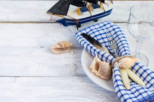Сервировка стола в морском стиле на тарелке с ракушками