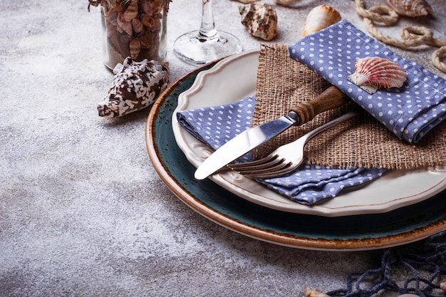 Marine style table setting with sea shells, fishnet and rope. selective focus