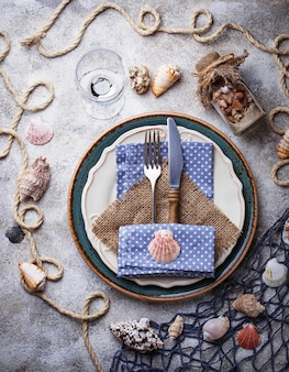Marine style table setting with sea shells, fishnet and rope. top view