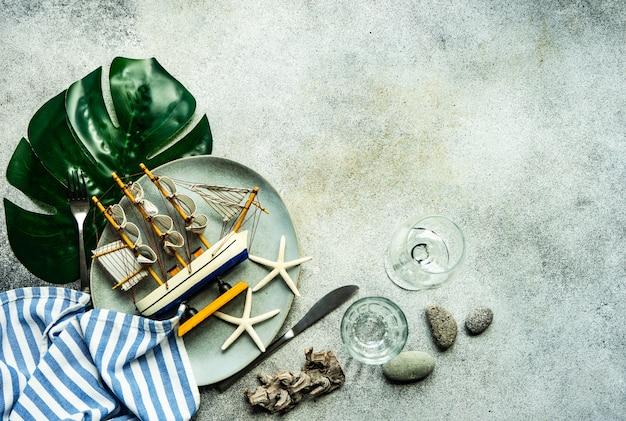 Морская сервировка стола на бетонном столе как концепция летнего фона