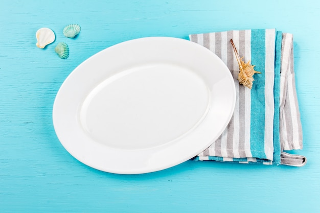 Marine table setting with white plate and sea decorations shells on wood blue
