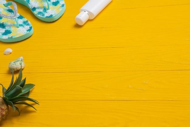 黄色い木製の床に置かれた海の旅、日焼け止めクリーム、スリッパ、パイナップル。