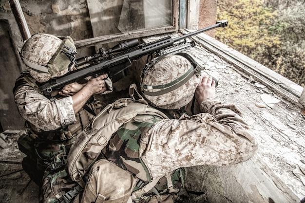 폐허가 된 도시 건물에 숨어있는 대구경의 대물 스나이퍼 라이플으로 무장 한 해병 저격 팀은 대피소에서 멀리 떨어진 적 목표를 쏘고 매복에 앉아 있습니다. 도시에서 군사 총격전